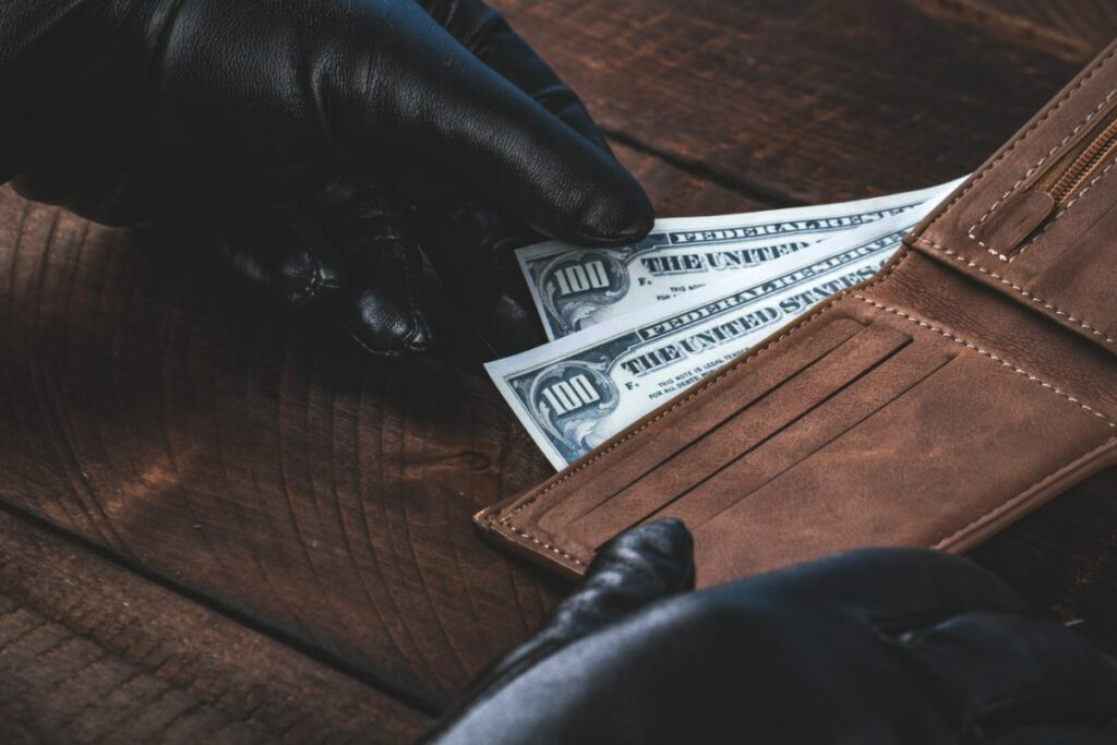 Black Gloves taking money from Wallet