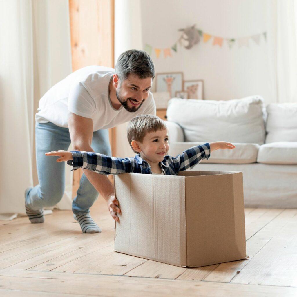 Father pushing son in a cardboard box