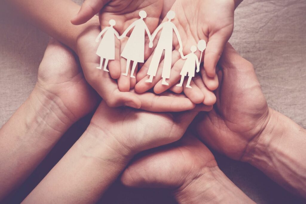 Hands holding paper figures